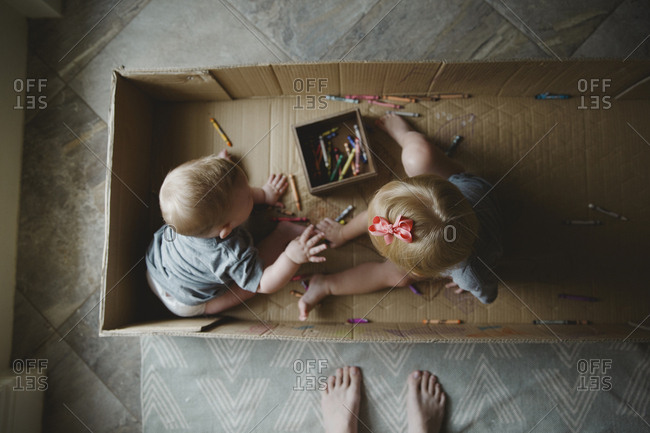 Brother and sister coloring while sitting in a cardboard box