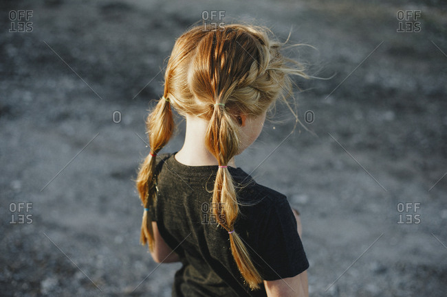 Red haired girl with pigtails looking down