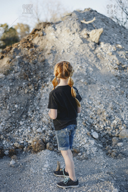 Red headed girl standing in front of a dirt hill looking away