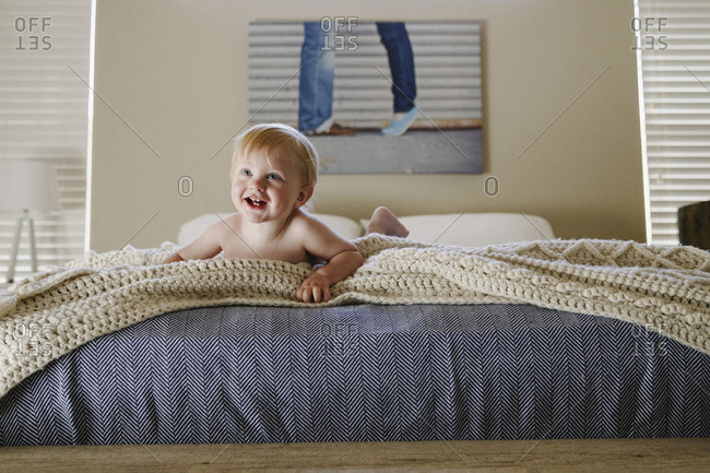 Baby boy laying on edge of bed laughing