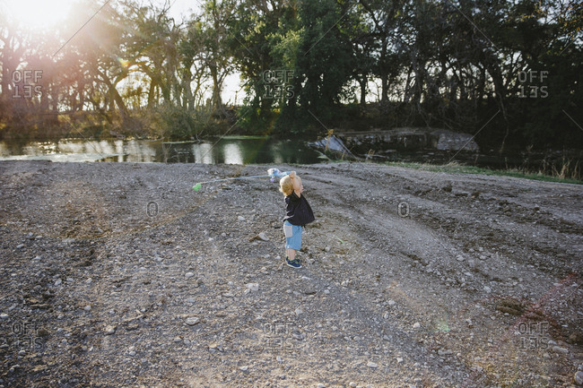 Toddler boy casting kid fishing pole at the creek