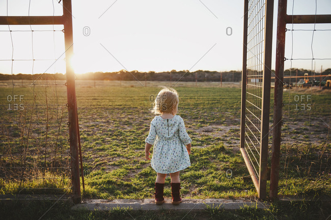 Little girl looking off at sunset on a farm