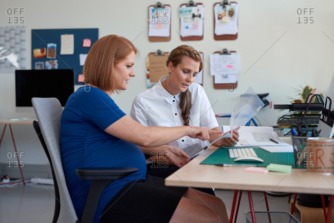 Pregnant manager giving pointers to female colleague in trendy open plan office creative environment