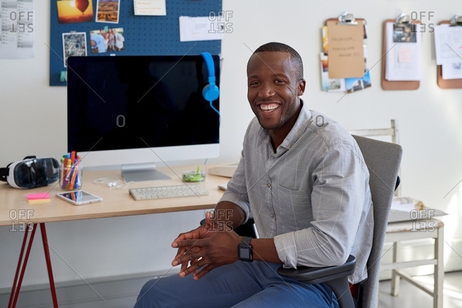 Portrait of confident professional black african man in trendy creative office, smiling satisfied happy with work