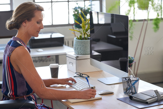 Hardworking woman in trendy modern office, writing reminder notes while on computer