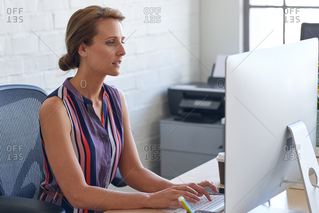 Female corporate worker concentrating working at her computer, sitting by desk with good posture