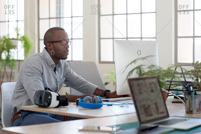Portrait of confident successful black african business man working at laptop computer in trendy open plan office