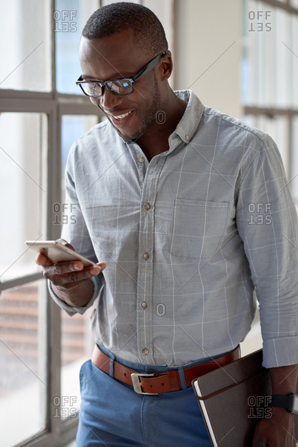 Confident successful african businessman smiling and looking at mobile cell phone, always connected to customers