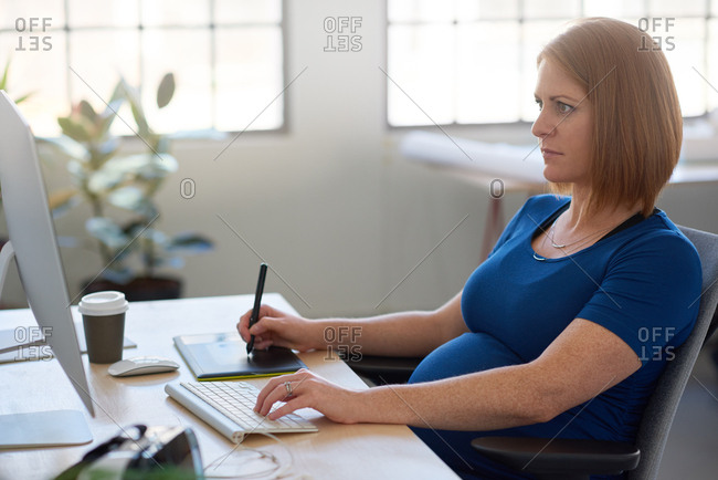 Heavily pregnant business woman manager team leader entrepreneur working in bright creative office