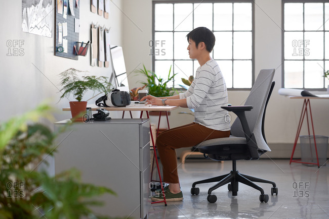Young asian woman in a open plan start up office, bright creative space with lots of plants
