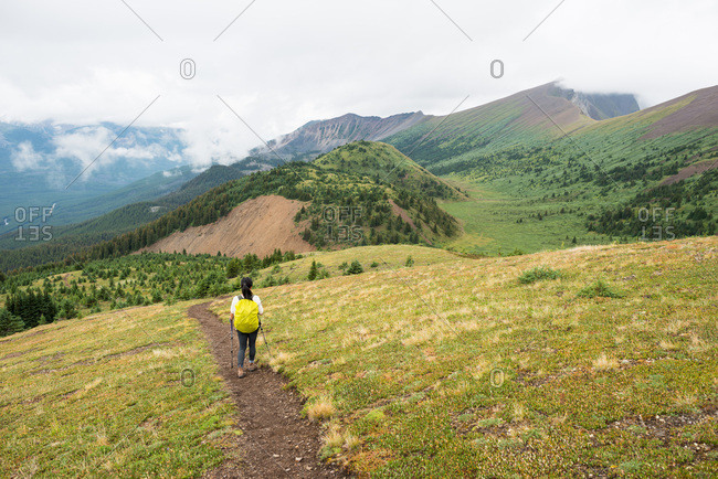 Female hiker walks along mountain trail with green valley behind her