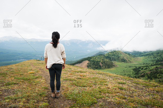 Female hiker surveys view of lush green mountain valley below
