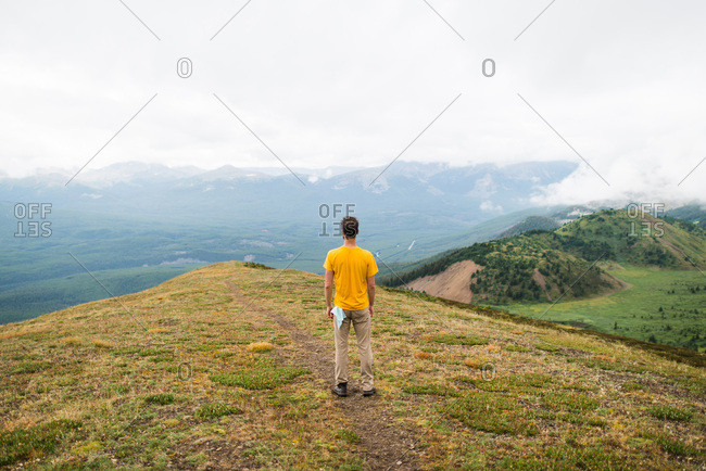 Male hiker surveys view of lush green mountain valley below