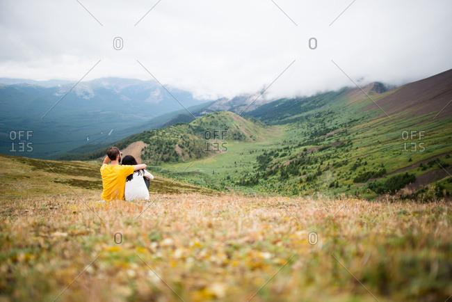 Couple sitting enjoys view of lush green mountain valley