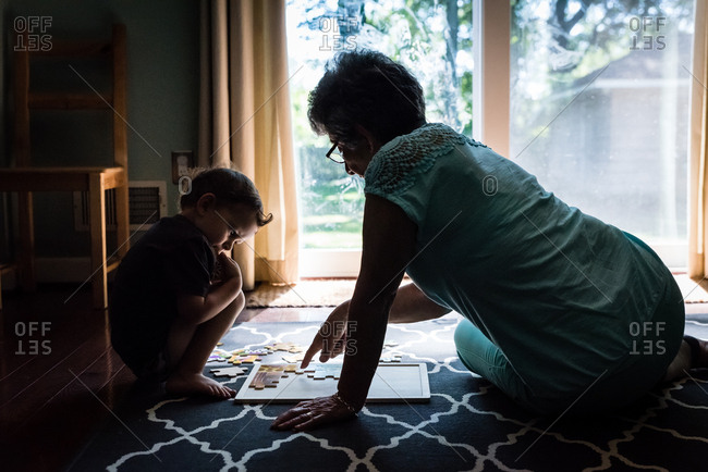 Woman solving puzzle with boy