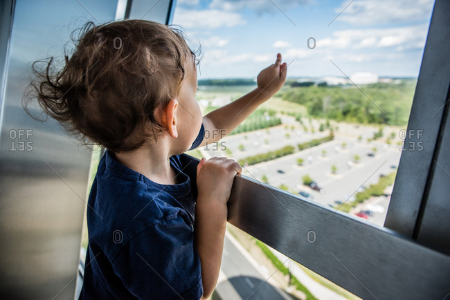 Child looking out high rise window