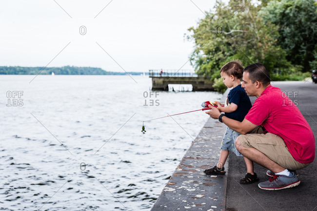 Dad and boy fishing at river's edge