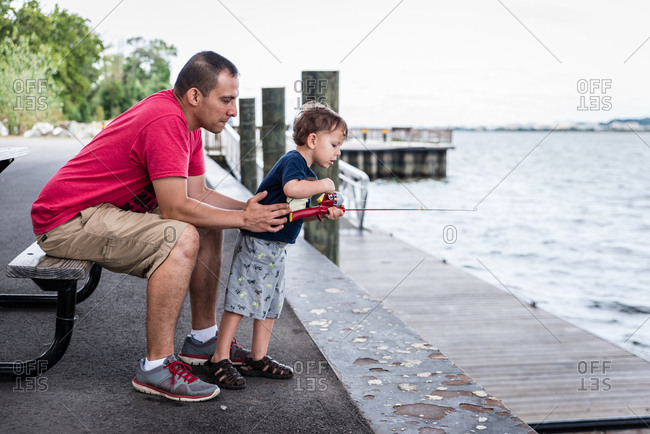 Dad and boy fishing from picnic table