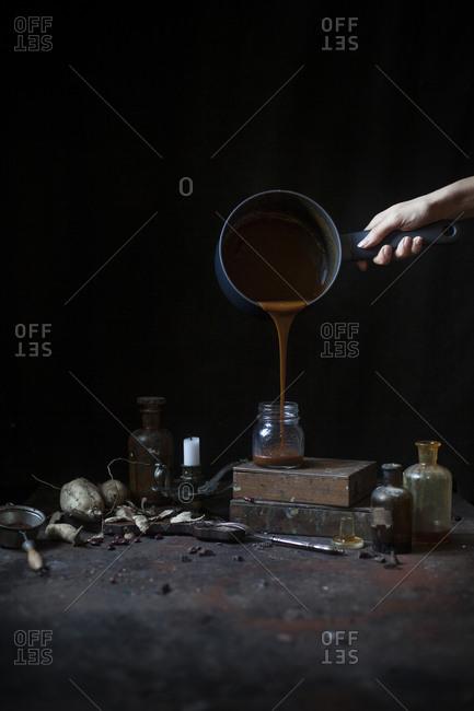 Person pouring homemade caramel sauce into a jar