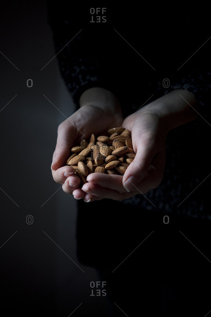 A young woman holds almonds in her hands on a dark background