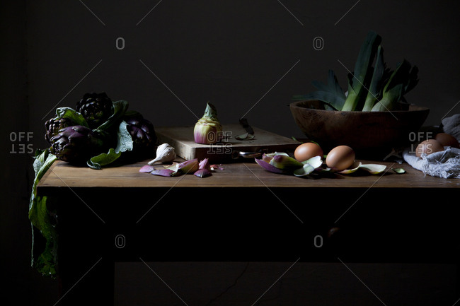 Kitchen table with fresh ingredients: artichokes, leeks, eggs and garlic