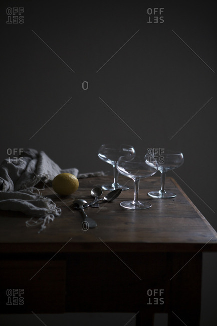 Three cocktail glasses on a kitchen table with a lemon, spoons and a cloth