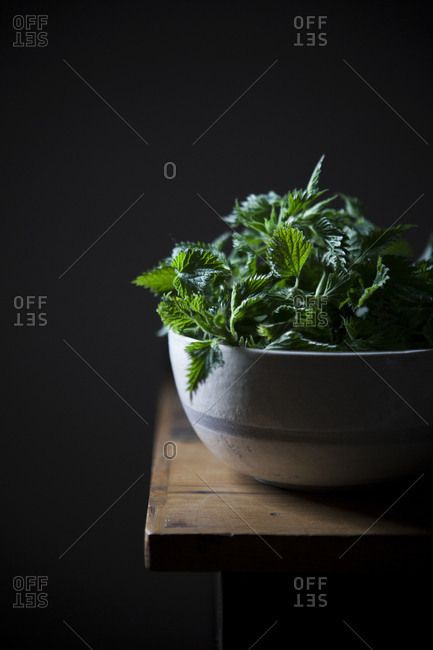 Fresh nettle leaves in a bowl on a wooden table