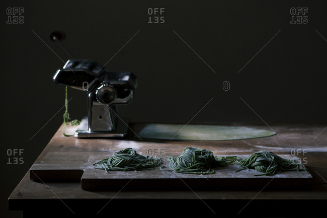 Homemade preparation of green pasta with pasta machine on a wooden table