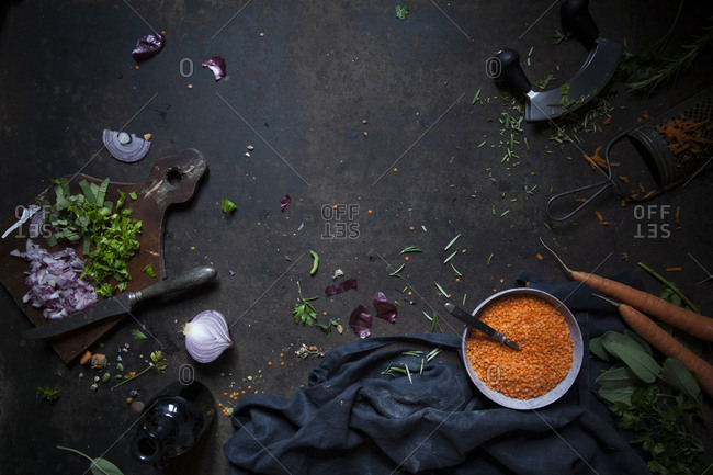 Overhead view of raw ingredients on a rusty surface: carrots, red lentils, chopped onion and parsley on a chopping board