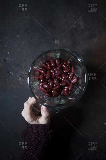 Overhead view of a hand holding a blender full of red beans ready to be blended