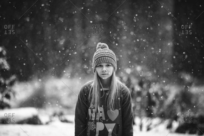 Girl standing as snow falls