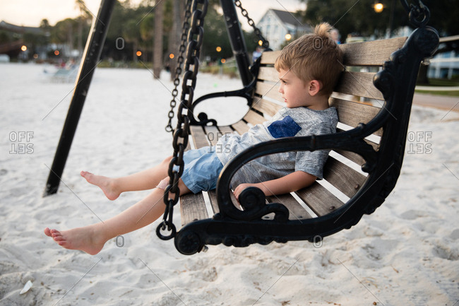 Boy on a swing at a beach