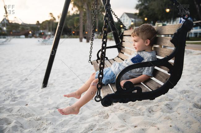 Boy on a swing on a beach