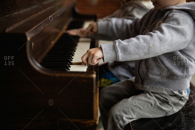Little kids playing at a piano
