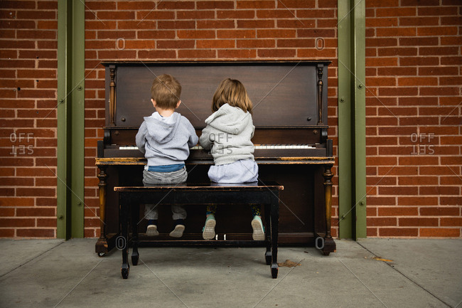 Boy and girl at a piano together
