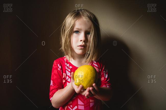 Girl holding a whole lemon