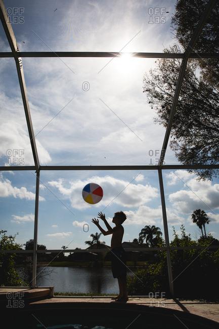 Boy throwing beach ball in air