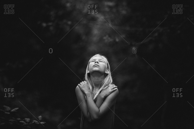 Girl with arms over chest in woods