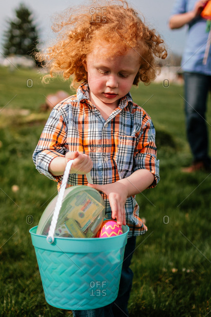 Child carrying basket of Easter eggs