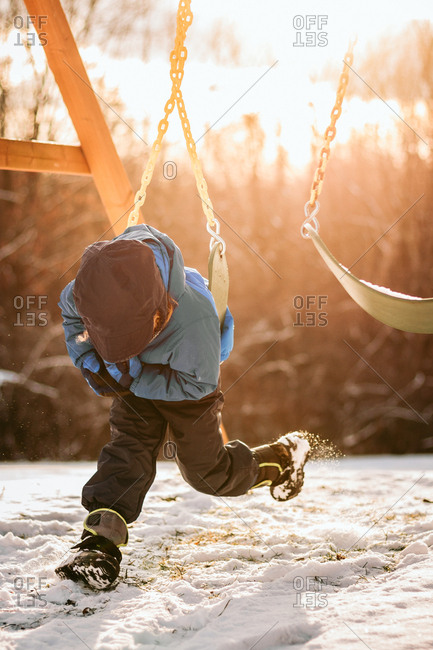 Child twisting on swing in snow