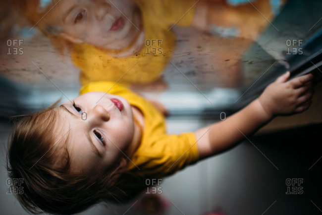 Toddler girl looking out dirty window