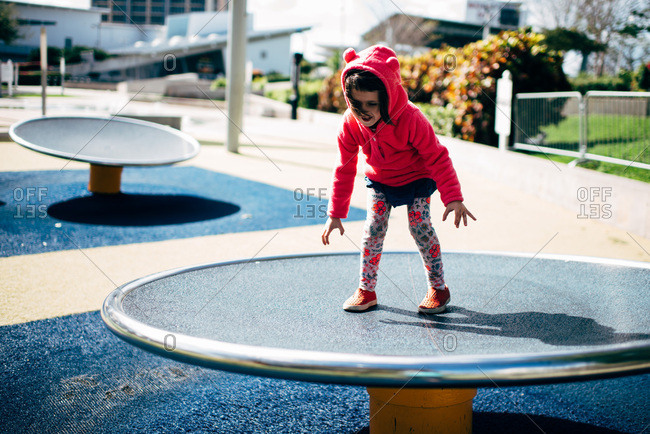 Girl playing and climbing on playground equipment alone