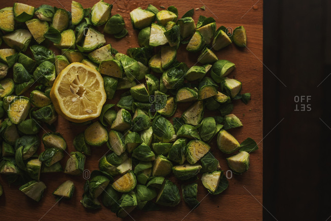 Chopped Brussels sprouts and a lemon on a cutting board