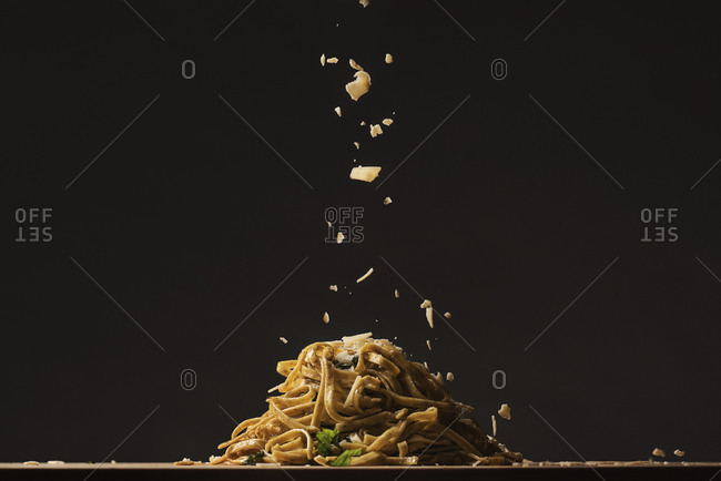 Parmesan being sprinkled onto a serving of linguine