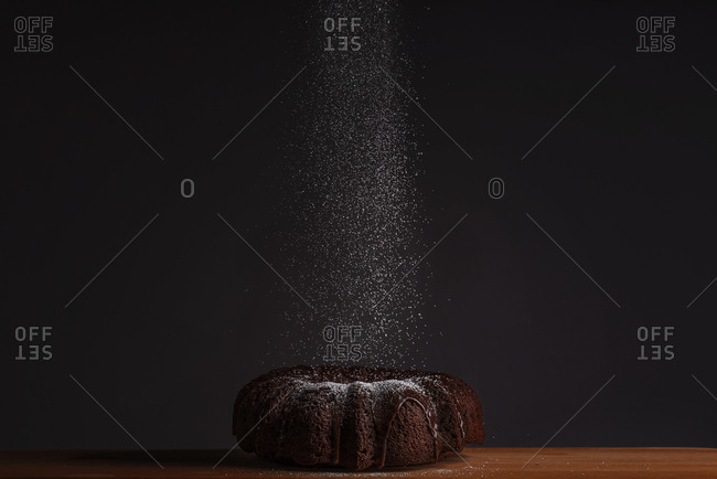Chocolate Bundt cake being dusted with powdered sugar