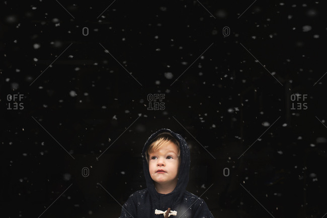 Little boy standing outside with snowflakes falling around him