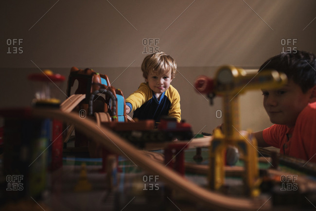 Brothers playing together with a toy train set