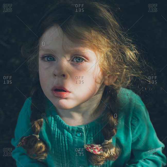 Little girl with tears in her eyes standing outside