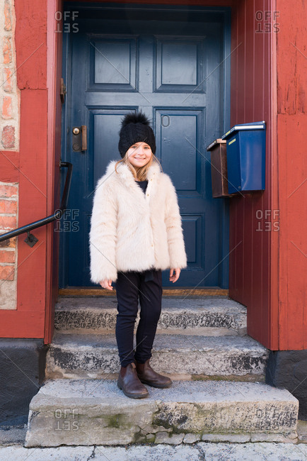 Girl in a furry coat and toboggan standing on a stoop
