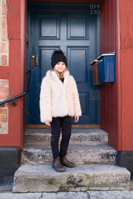 Girl standing on a stoop in a fur coat and toboggan